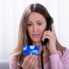 stockfresh_9186280_woman-holding-credit-card-while-talking-on-telephone_resized