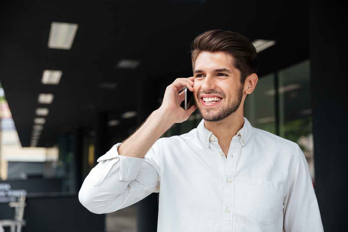 stockfresh_7574397_happy-young-businessman-talking-on-mobile-phone-near-business-center_resized